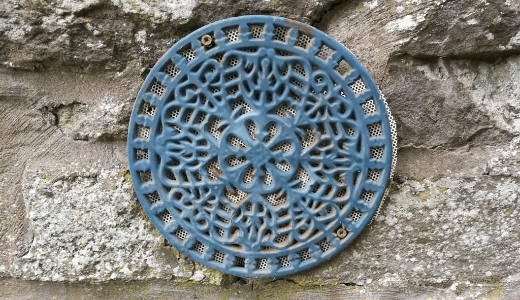 verdigris wrought iron disc on side of building