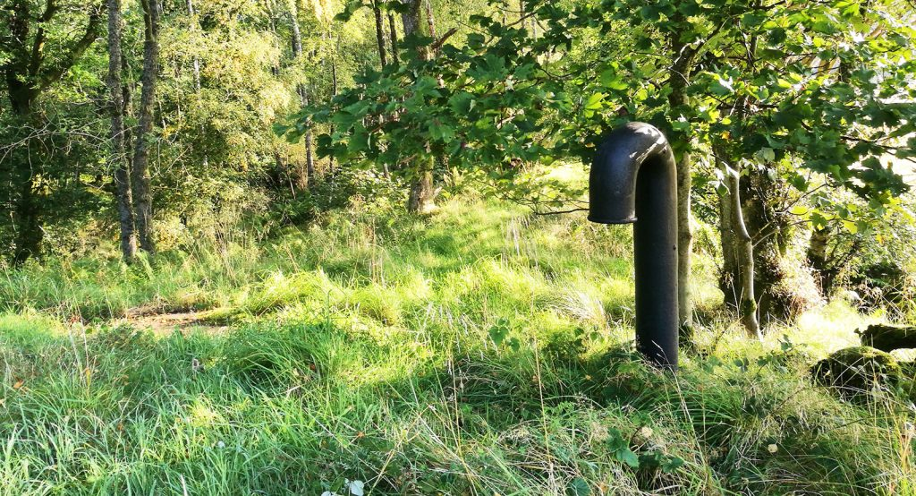 water pipe of some kind on top of a mound